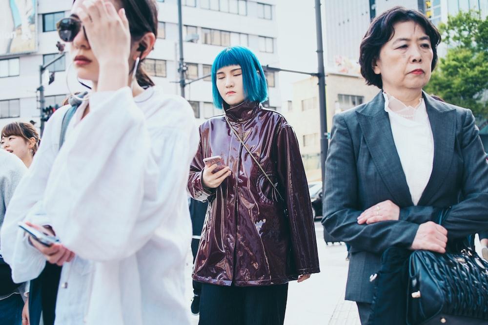 four women standing near white building