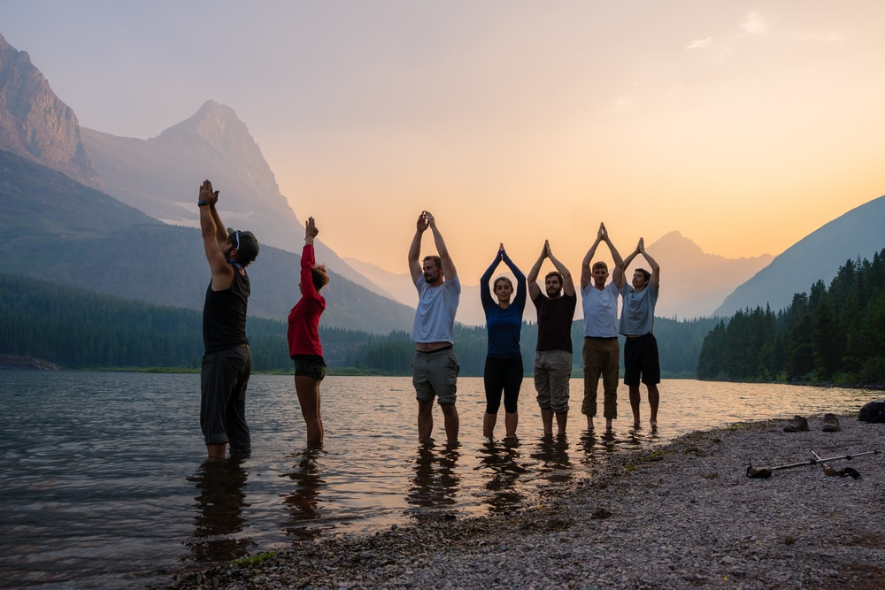 people standing on seashore while raising hands