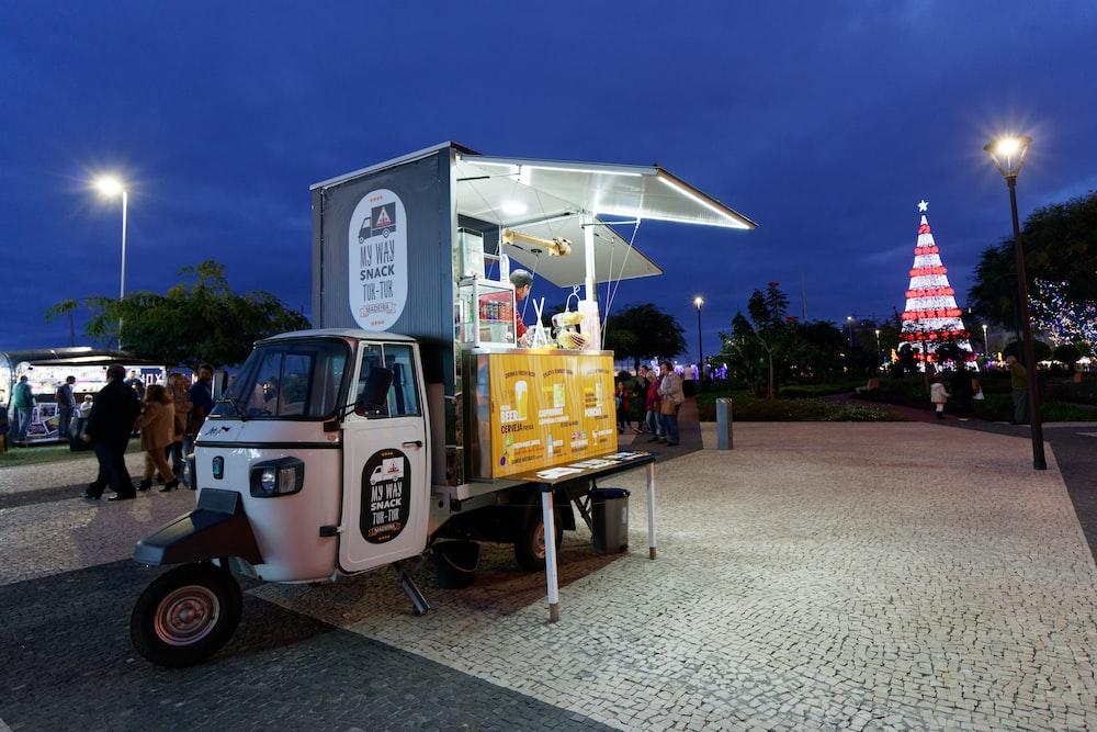 yellow and white auto rickshaw food stall