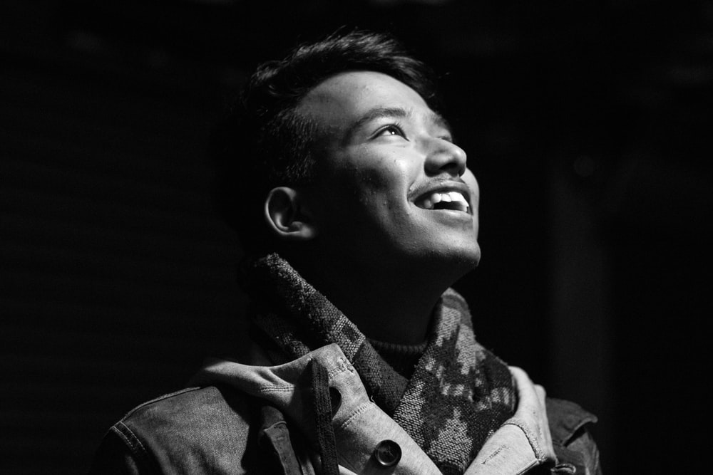 smiling man in grayscale photography