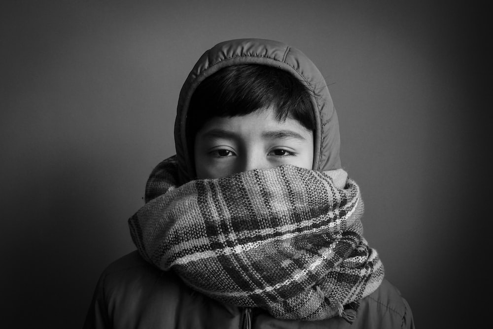 grayscale photography of person wearing hooded top and covering his mouth
