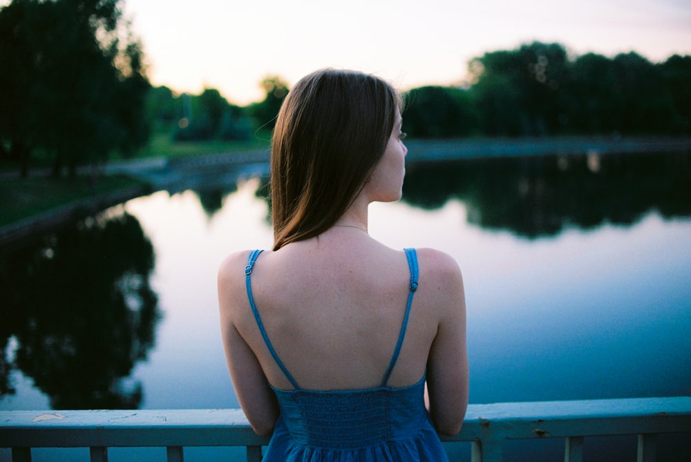 woman leaning on metal fence facing body of water