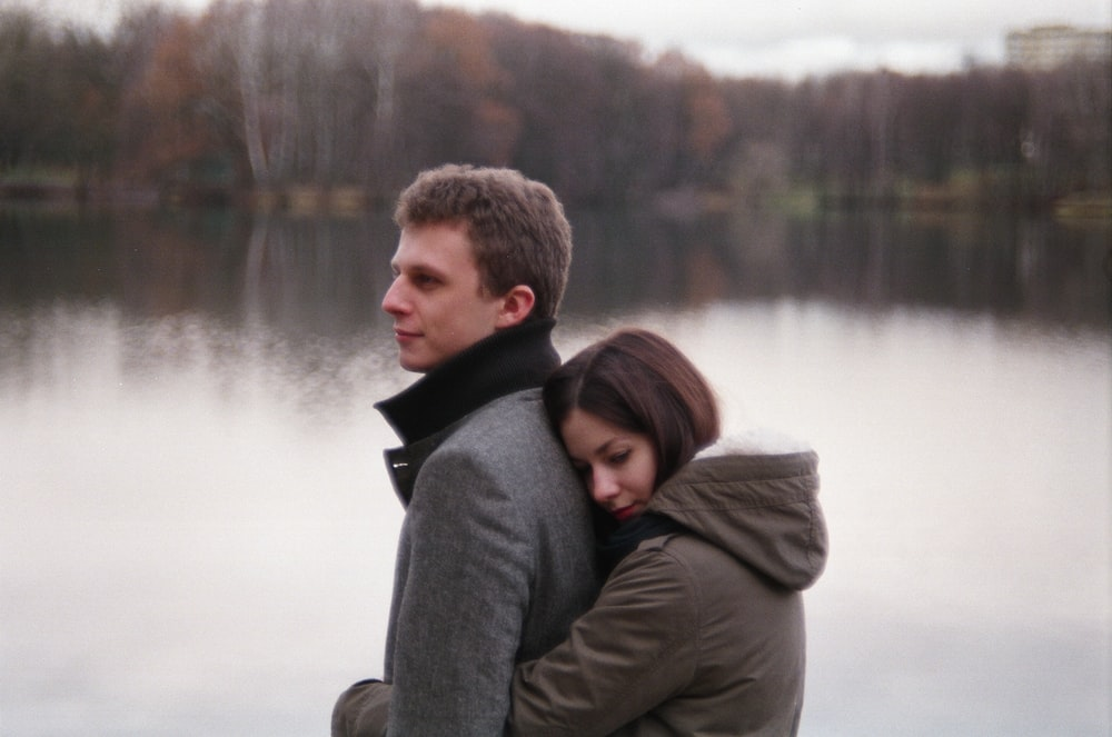 woman hugging man near body of water and trees during daytime