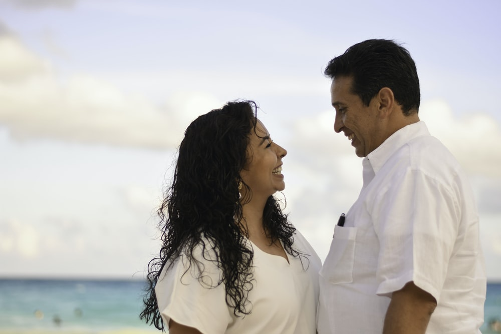 man and woman facing each other while smiling at the beach