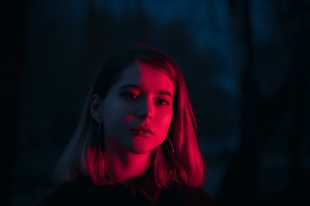 red lighting on woman's face at night