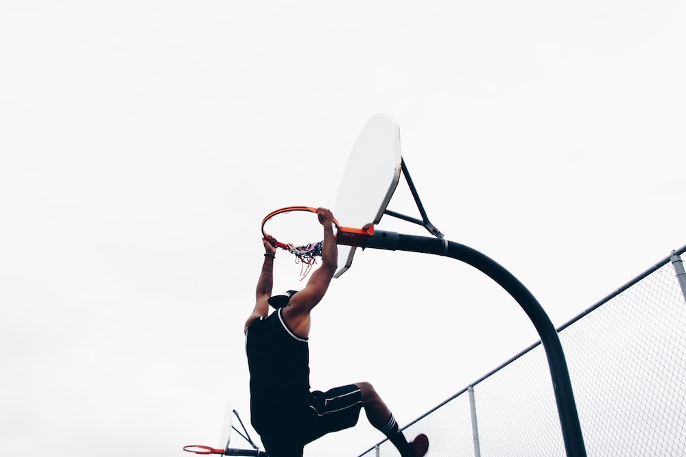 close-up photography of man dunking on basketball hop