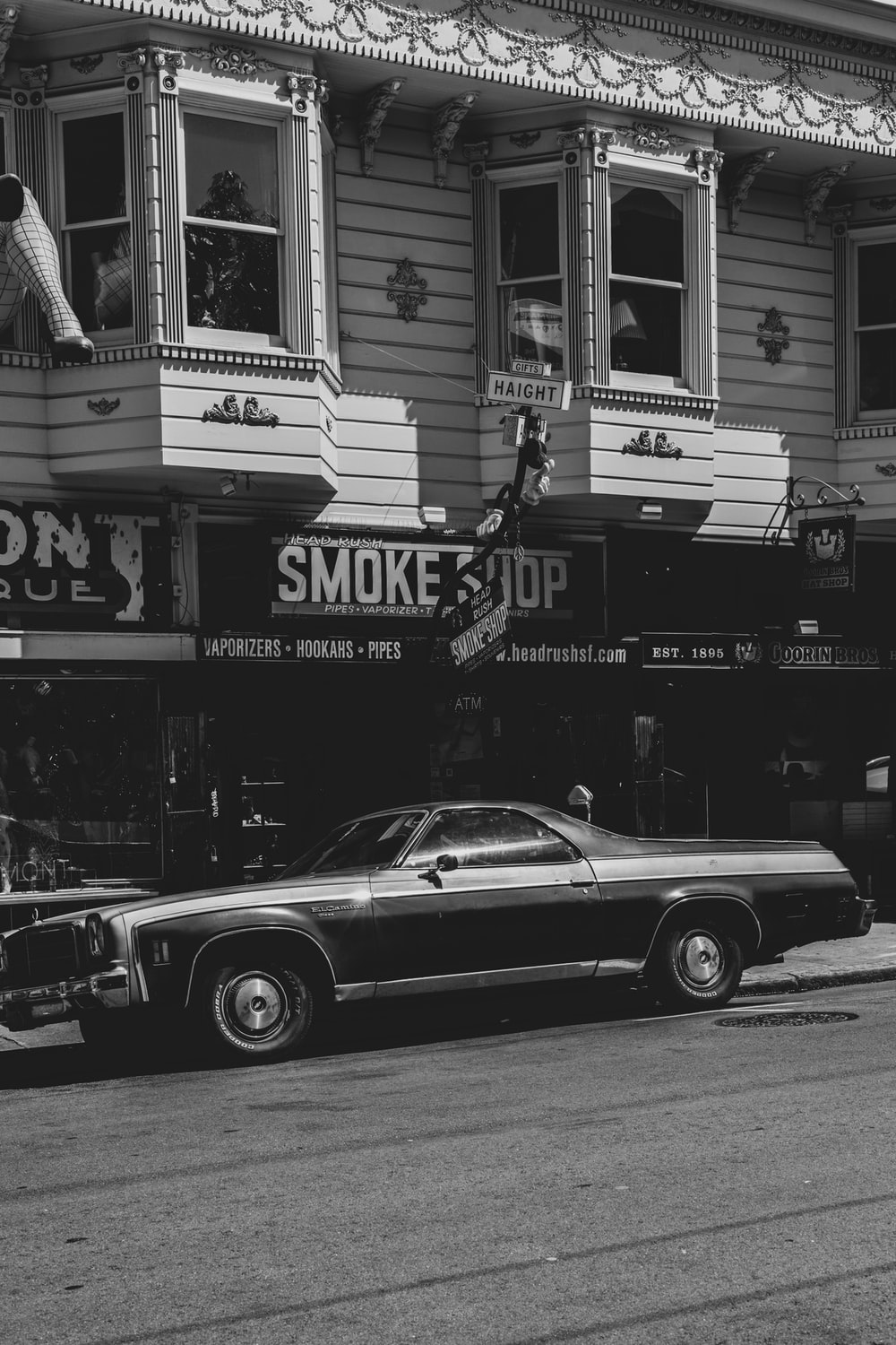 grayscale photo of coupe near building