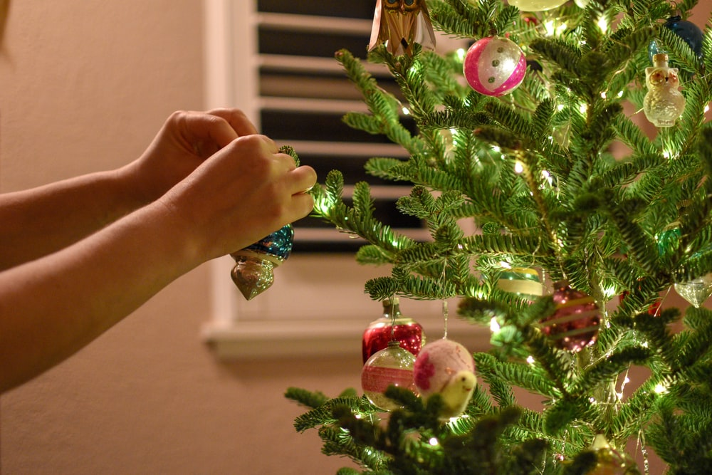 person putting baubles on Christmas tree