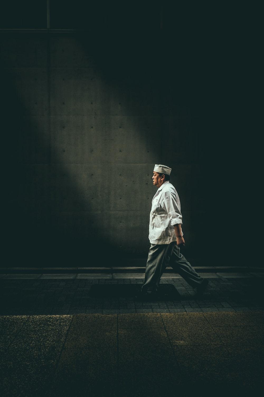 man in white shirt walking on street