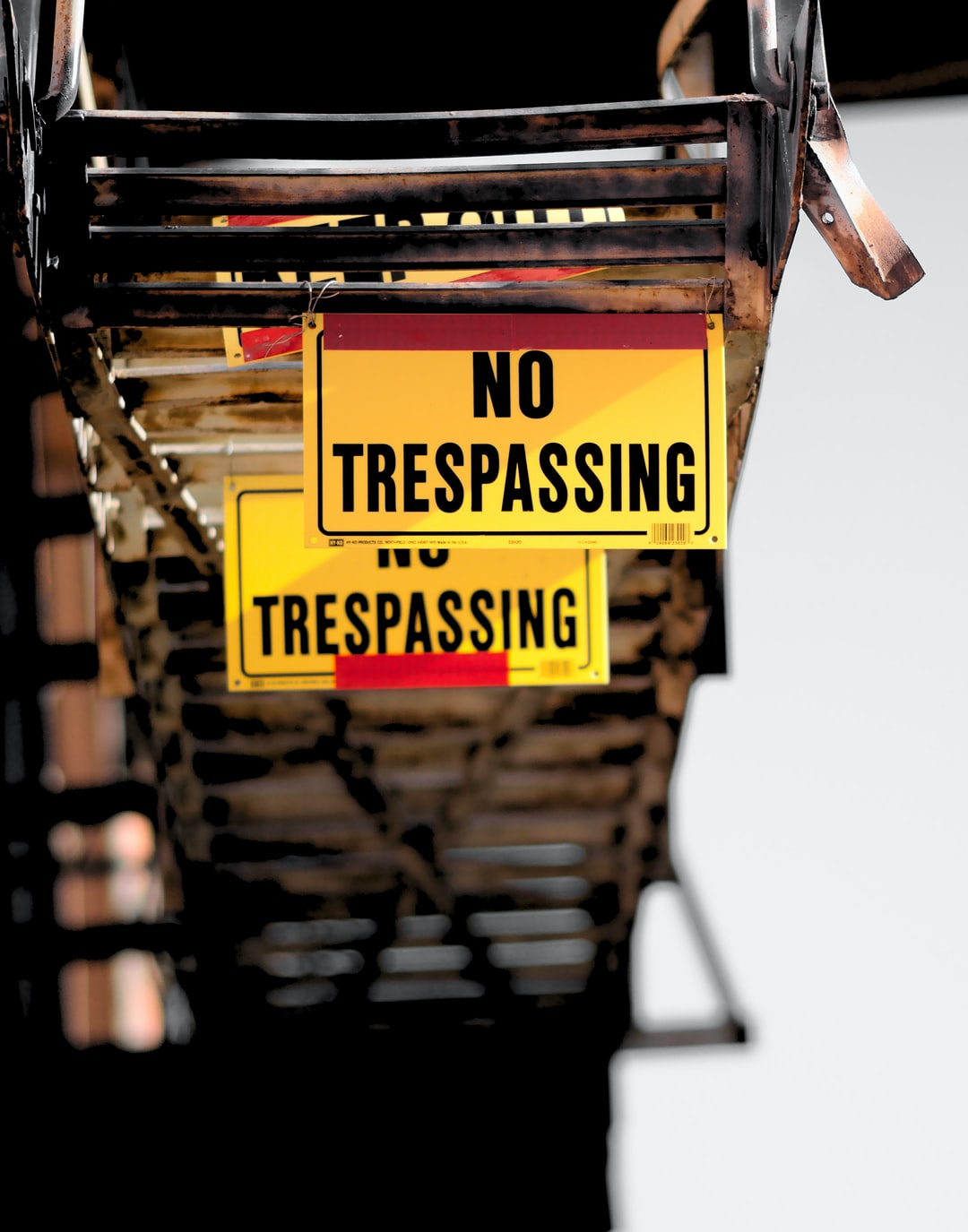 These NO TRESPASSING signs are hanging from a fire escape on a downtown building.
