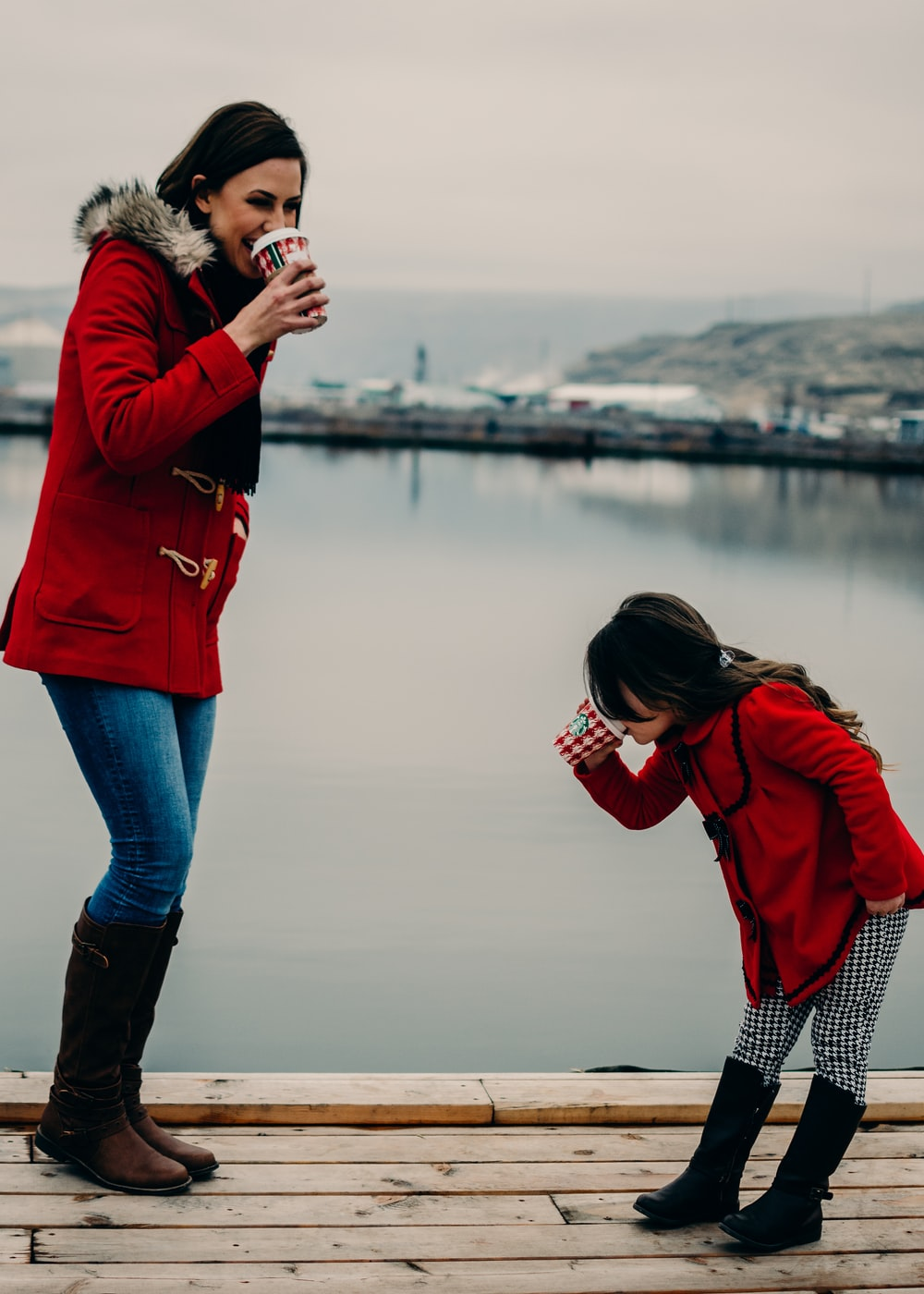 woman and girl drinking coffee during daytime