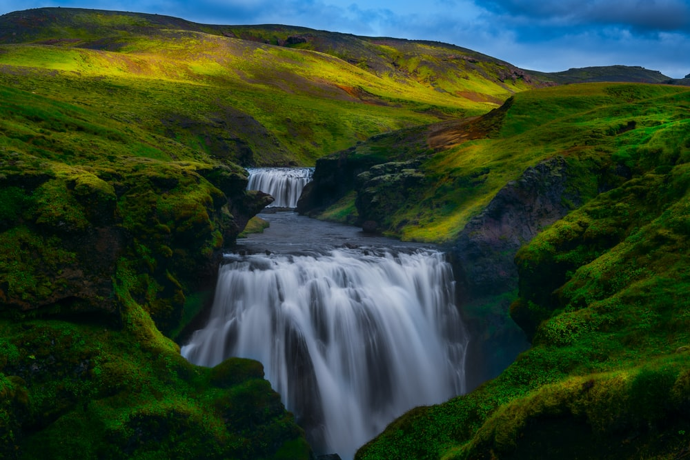 waterfalls between grass-covered hills during daytime