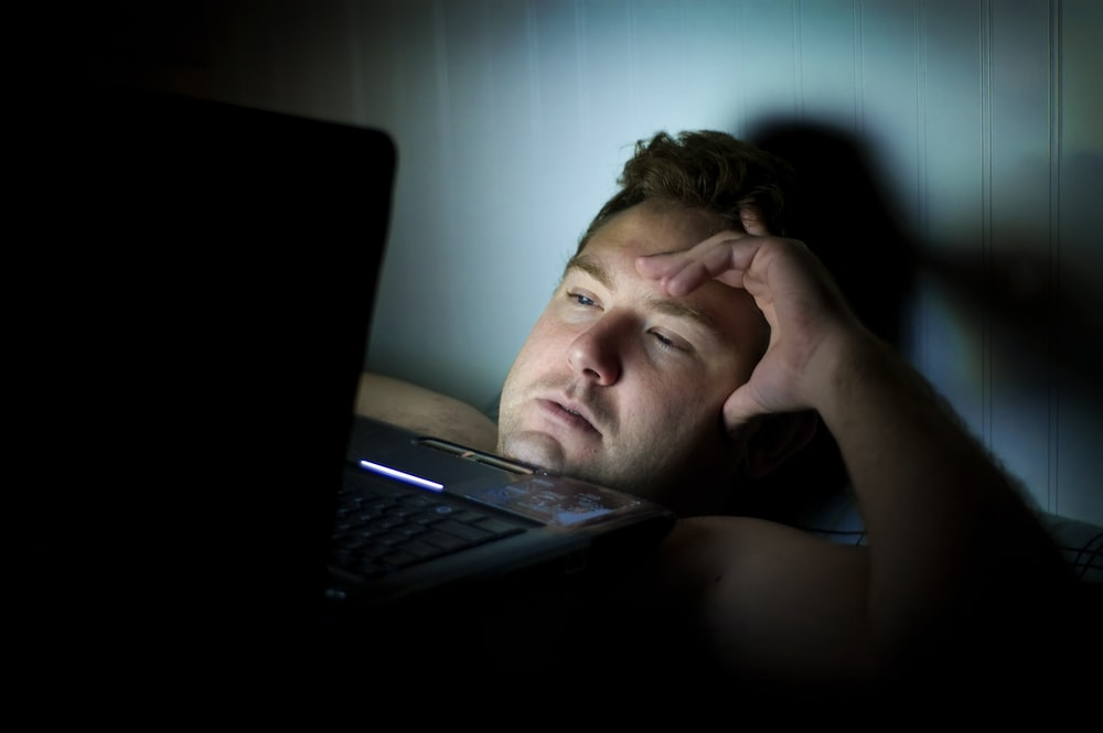 man lying on bed with laptop on top of chest watching something