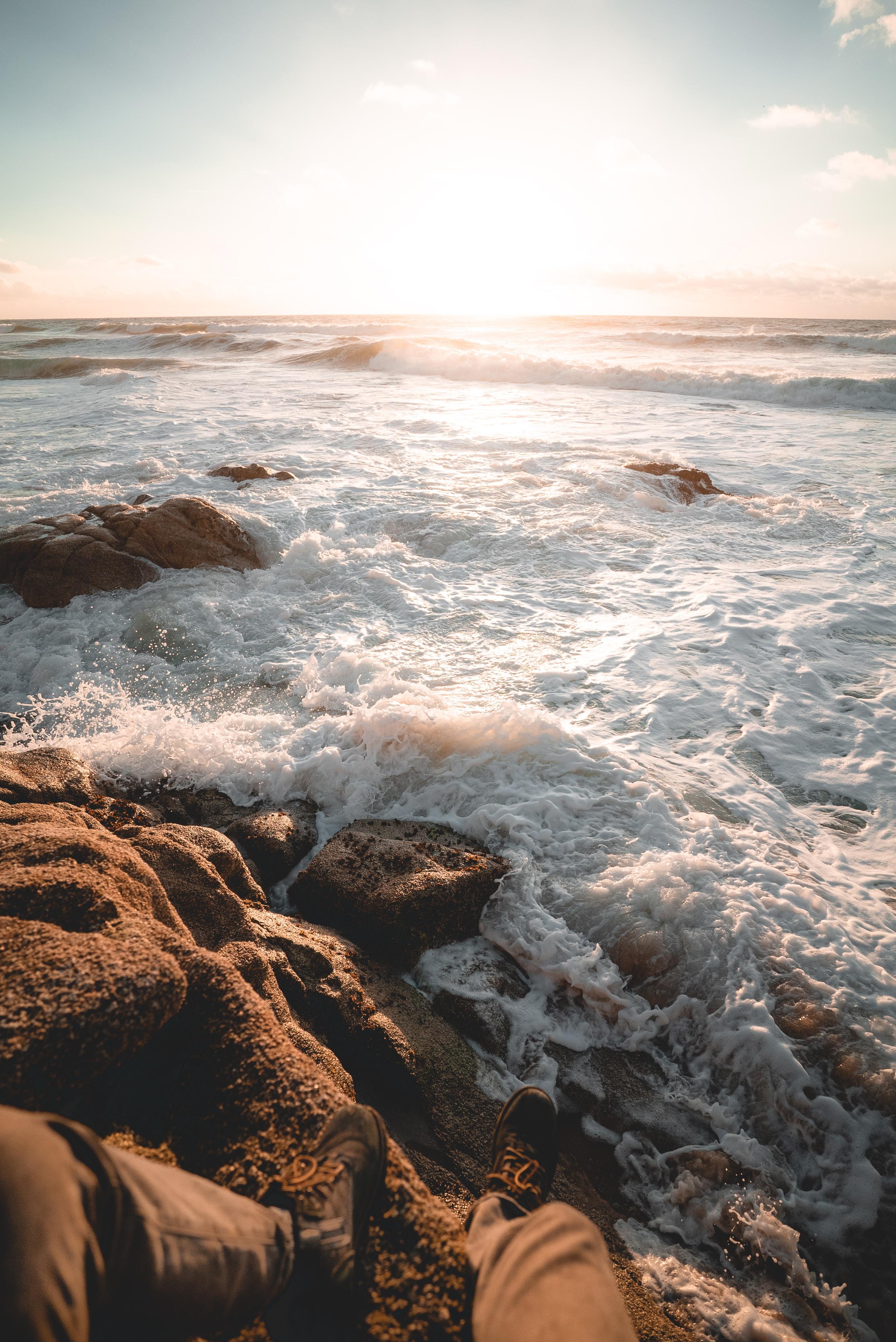 person sitting on rock beside beach