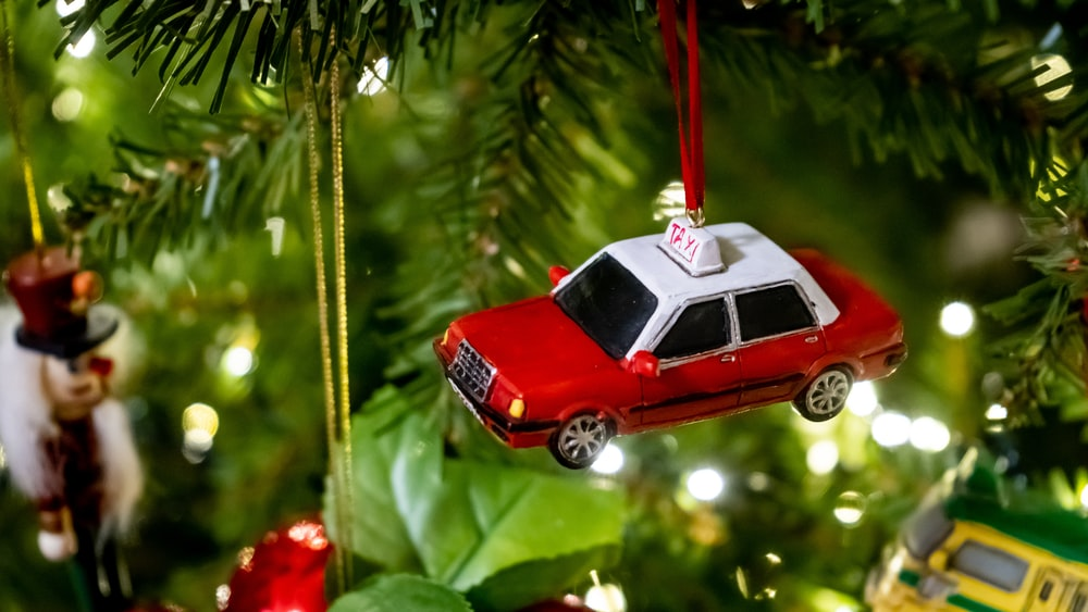 red and white car scale model hanging on green Christmas tree