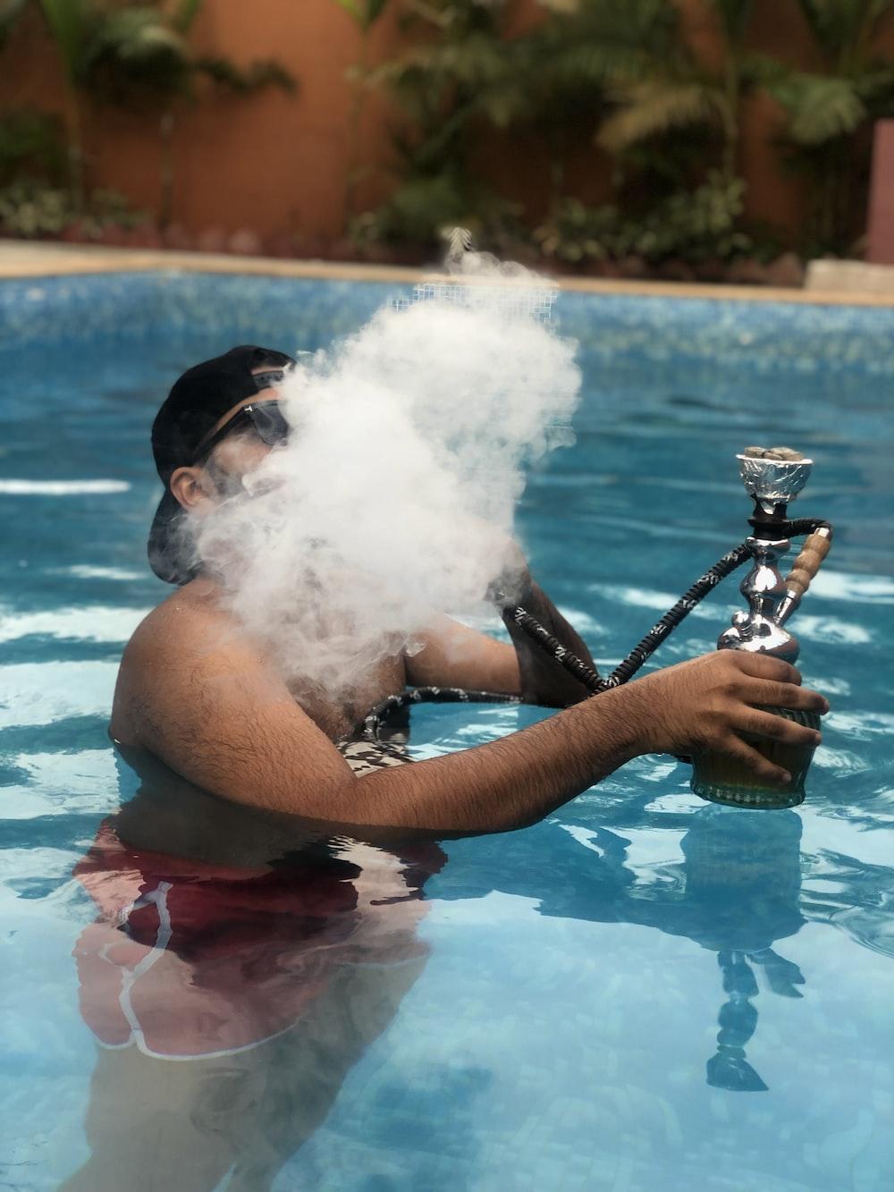man using hookah at swimming pool \