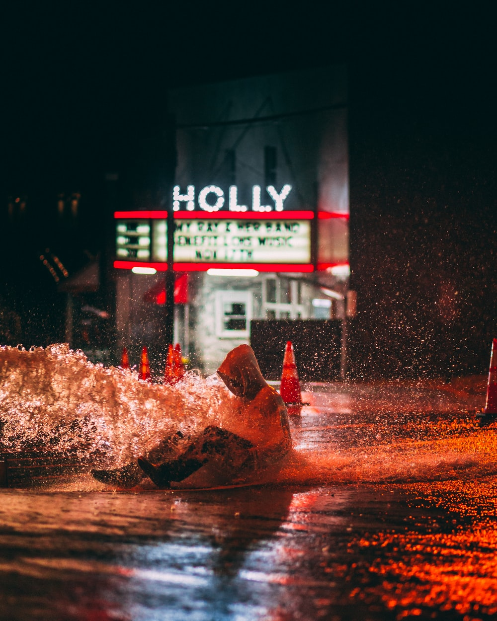 person sitting on watery road near Holly building