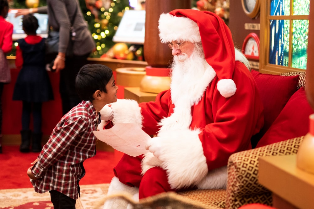 boy standing in front of man wearing Santa Claus costume