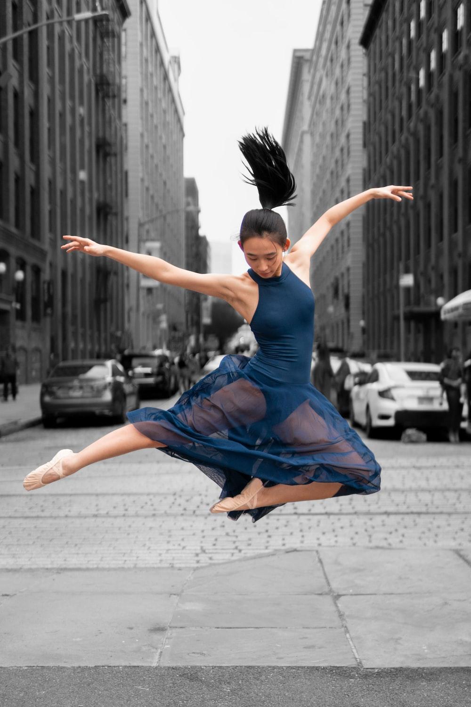 jumping ballerina wearing blue dress during daytime