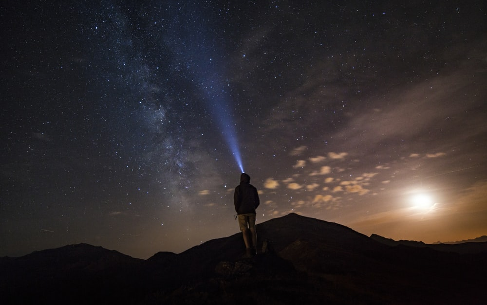 man standing at mountain peak under starry night sky