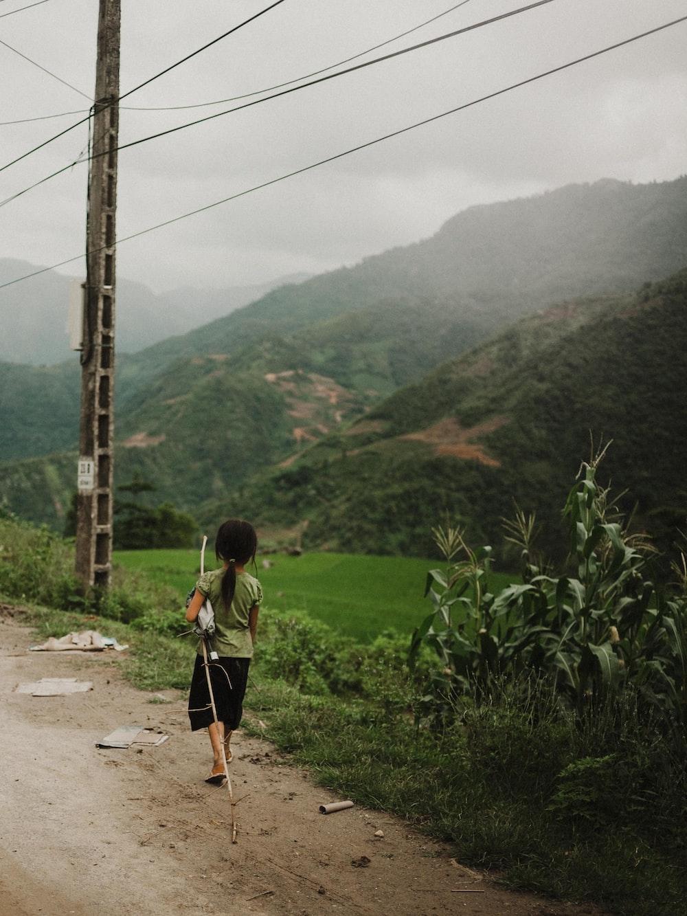 girl walking along rough road with mountain view