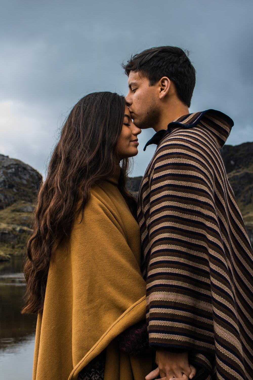 man kissing woman on forehead