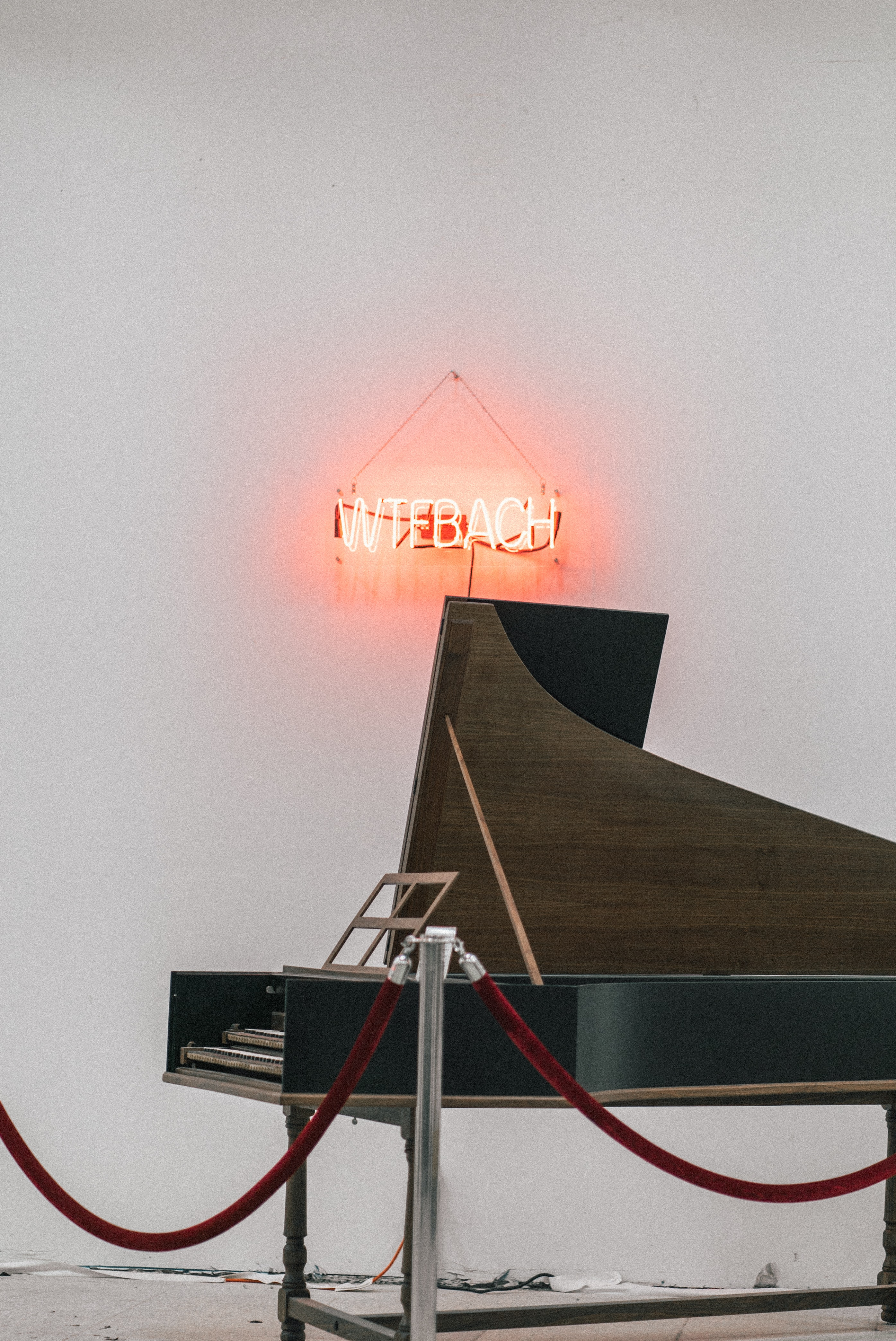 brown and black grand piano near white wall with turned-on neon signage
