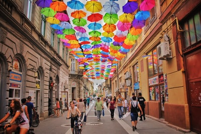assorted-color umbrella hanged above pathway near houses romania teams background