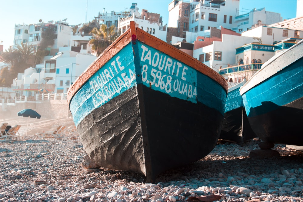 black and teal boat on seashore