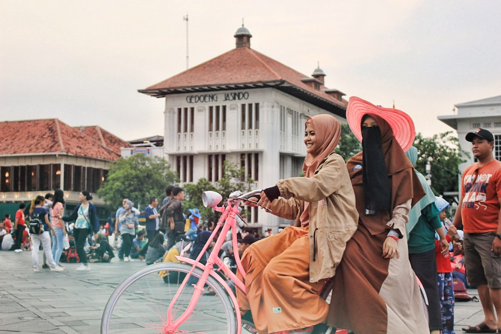 2 woman riding bike beside people by building during daytime