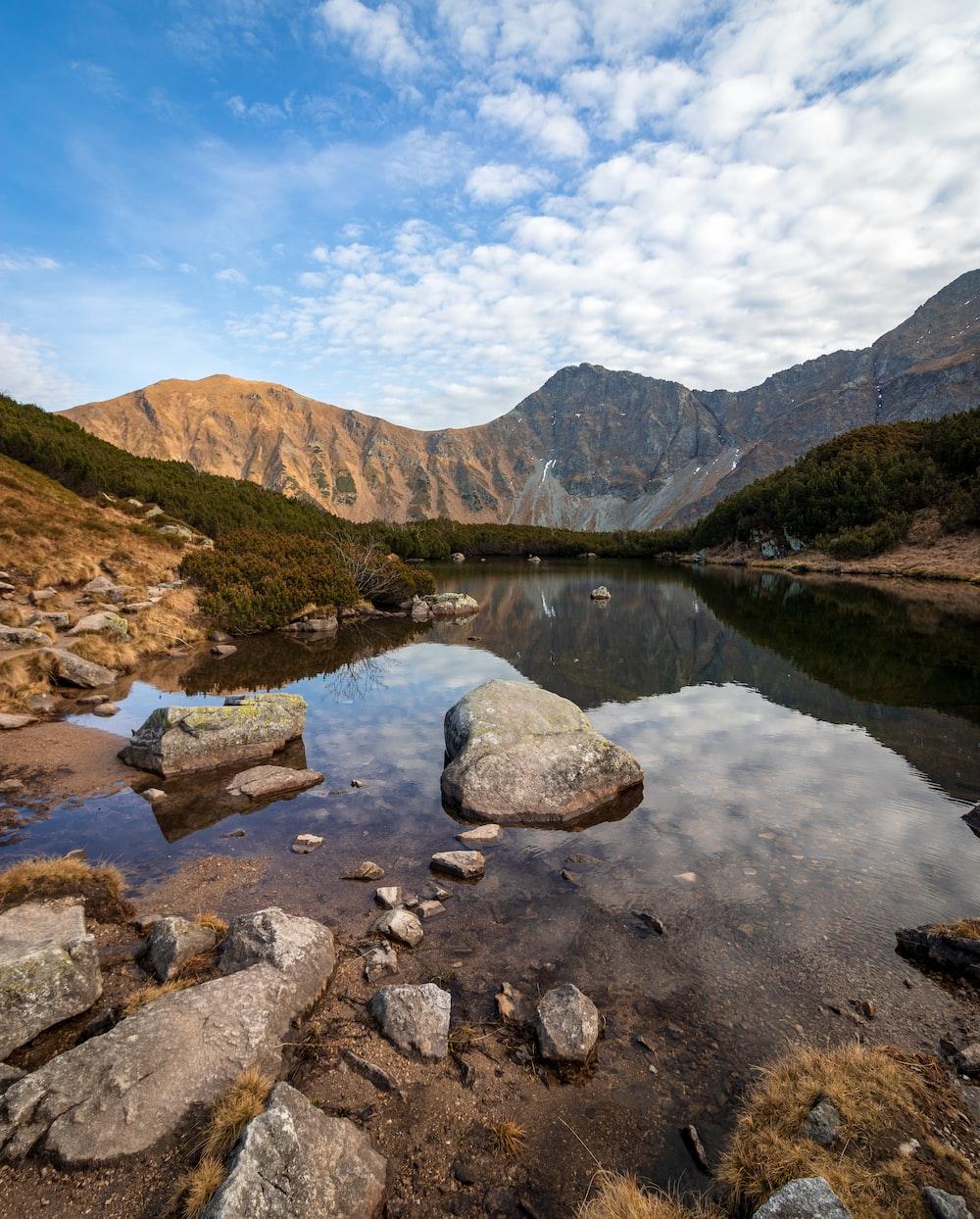 rocks in body of water facing mountain under blue sky
