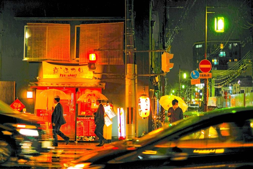 people walking on street holding umbrella under rain at nnight
