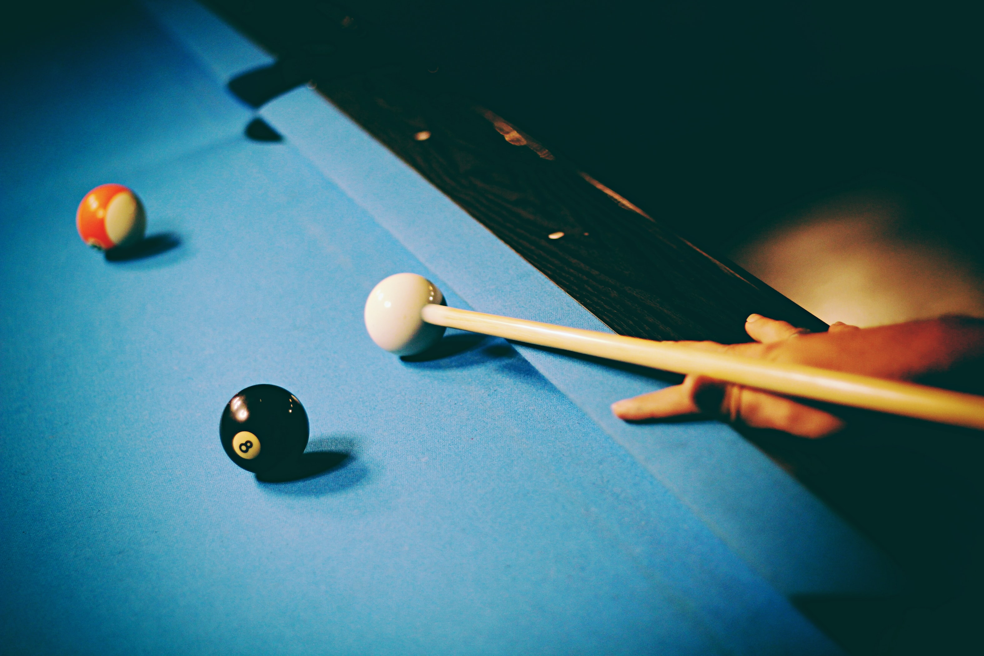 Vintage looking photo of person hitting white ball on pool table