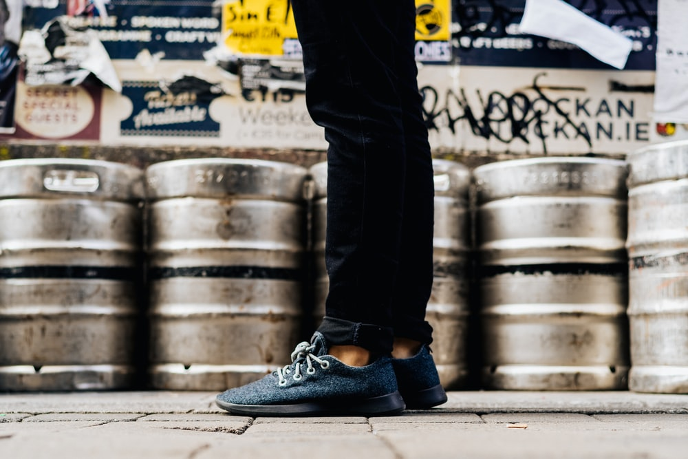 standing man wearing gray shoes beside cans
