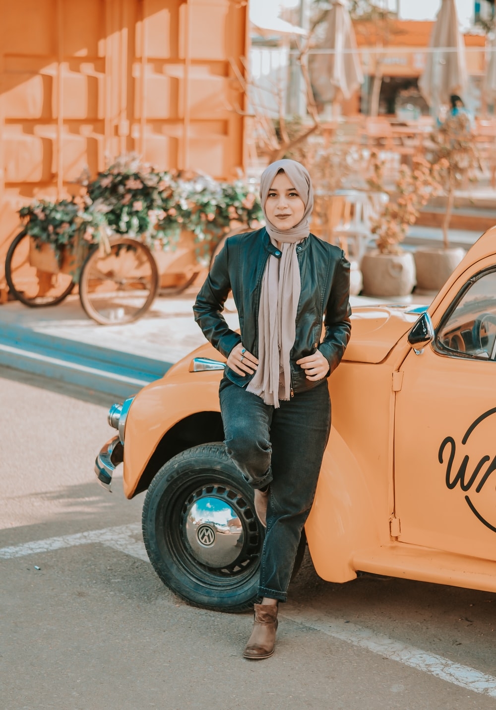 woman standing beside yellow vehicle