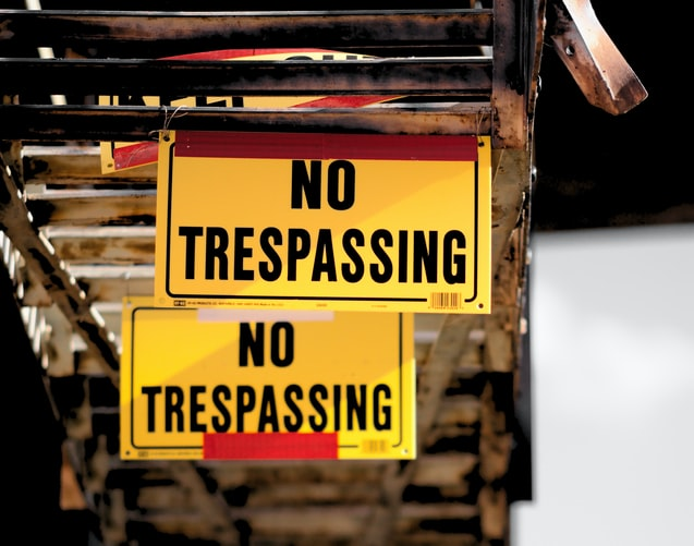 "A photo of two signs, one in front of the other, both say ""No Trespassing"" on them. They are bright yellow, hanging underneath a bridge or boardwalk."