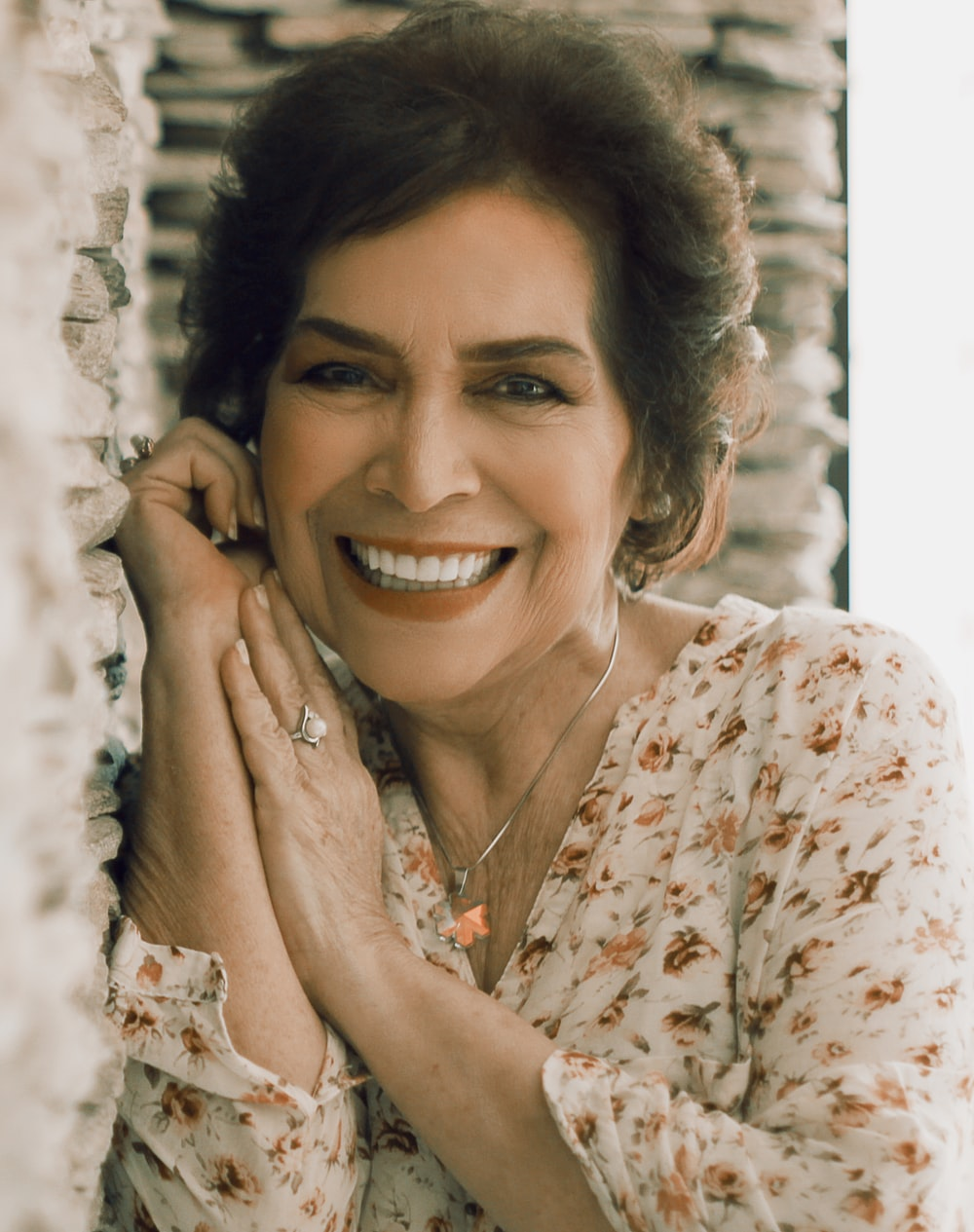 woman in white and orange floral shirt smiling
