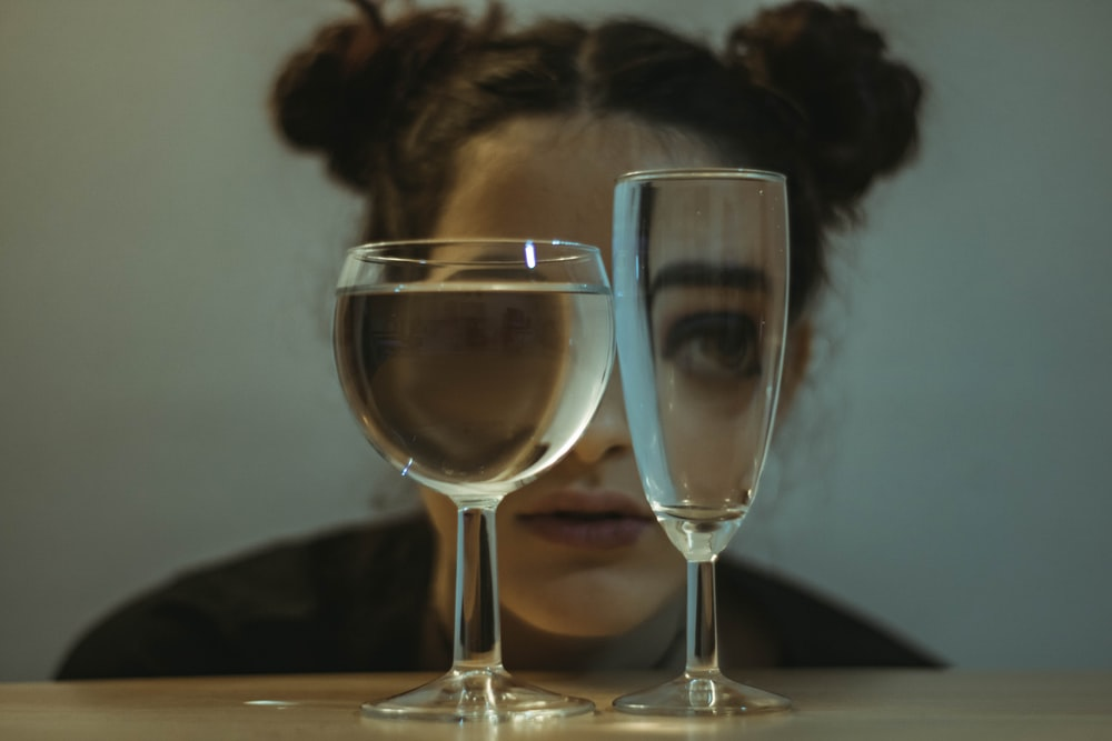 two clear drinking glasses on top of the table near woman