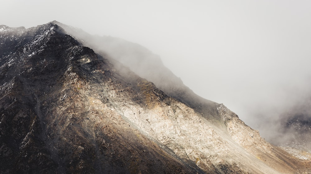 mountain covered with white smoke during daytime