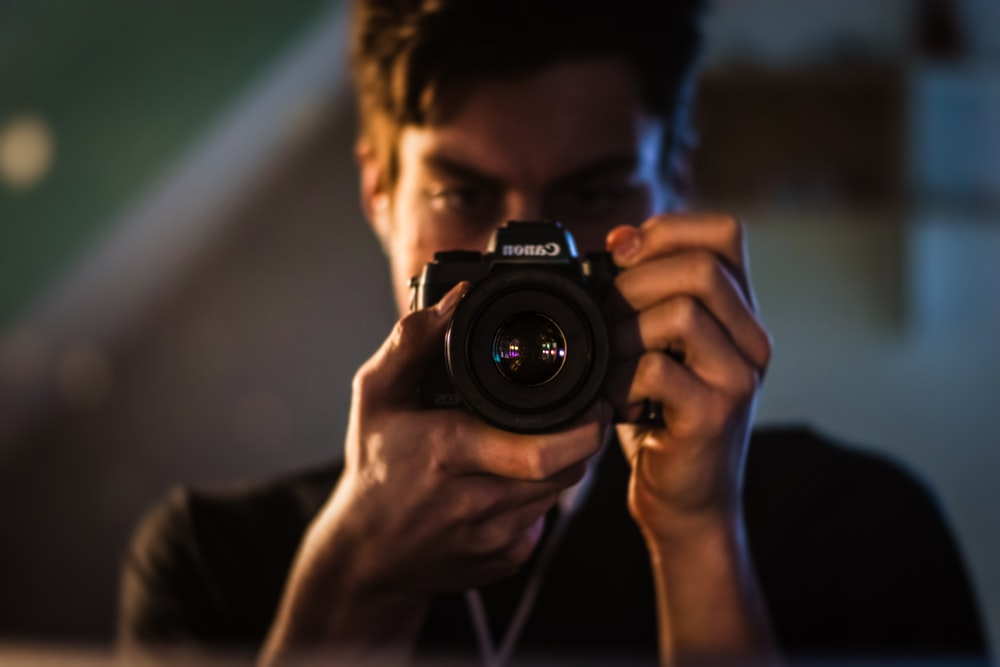 man holding Canon camera