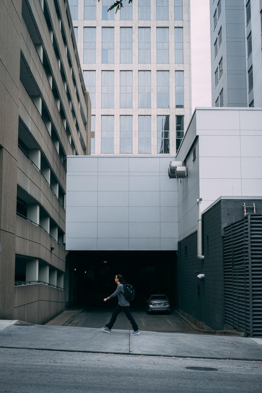 man walks past building driveway