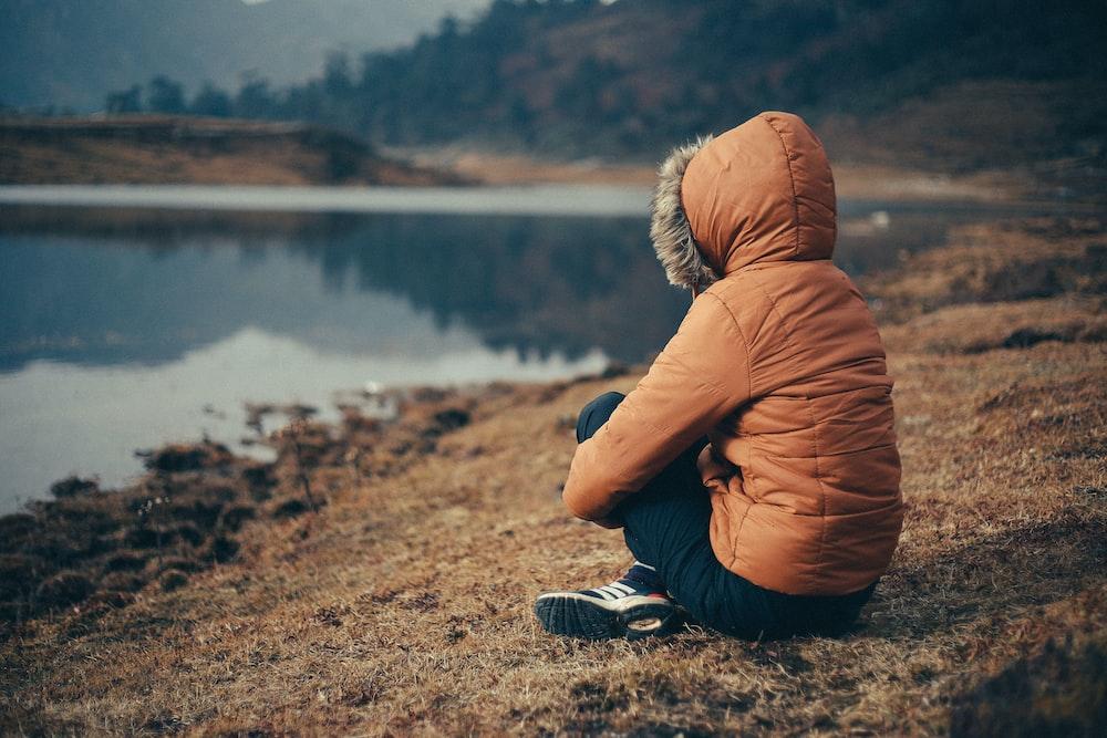 woman in orange parka sits on bank of lake