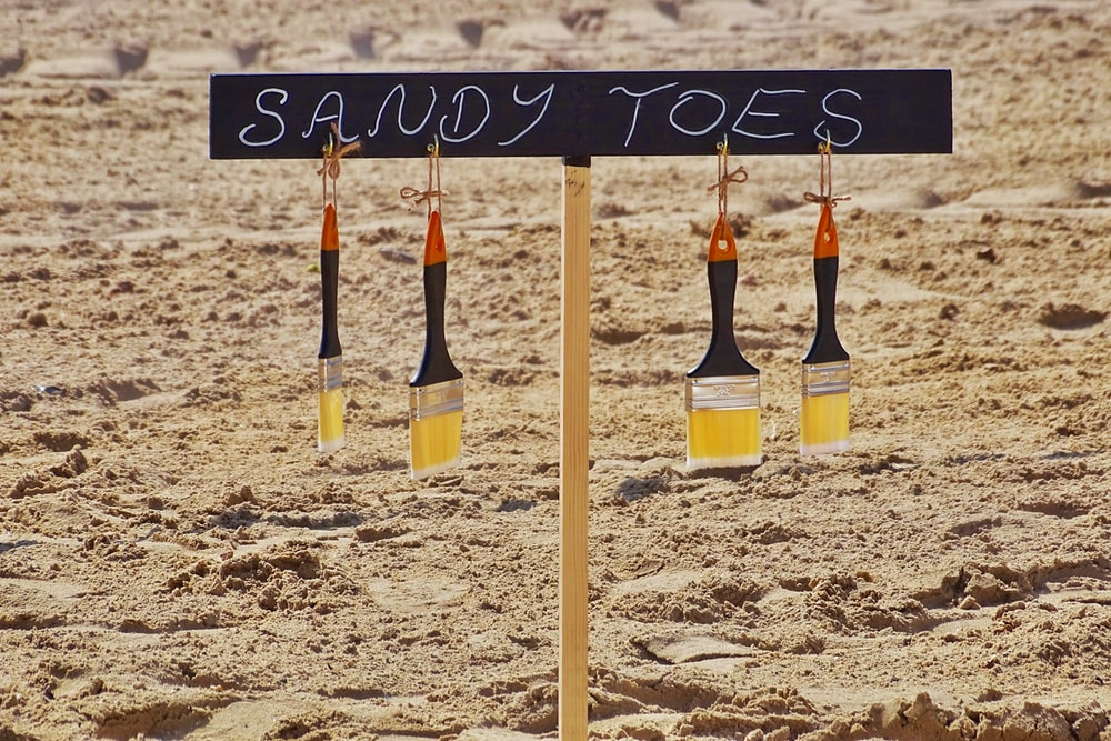 sandy toes sign during daytime