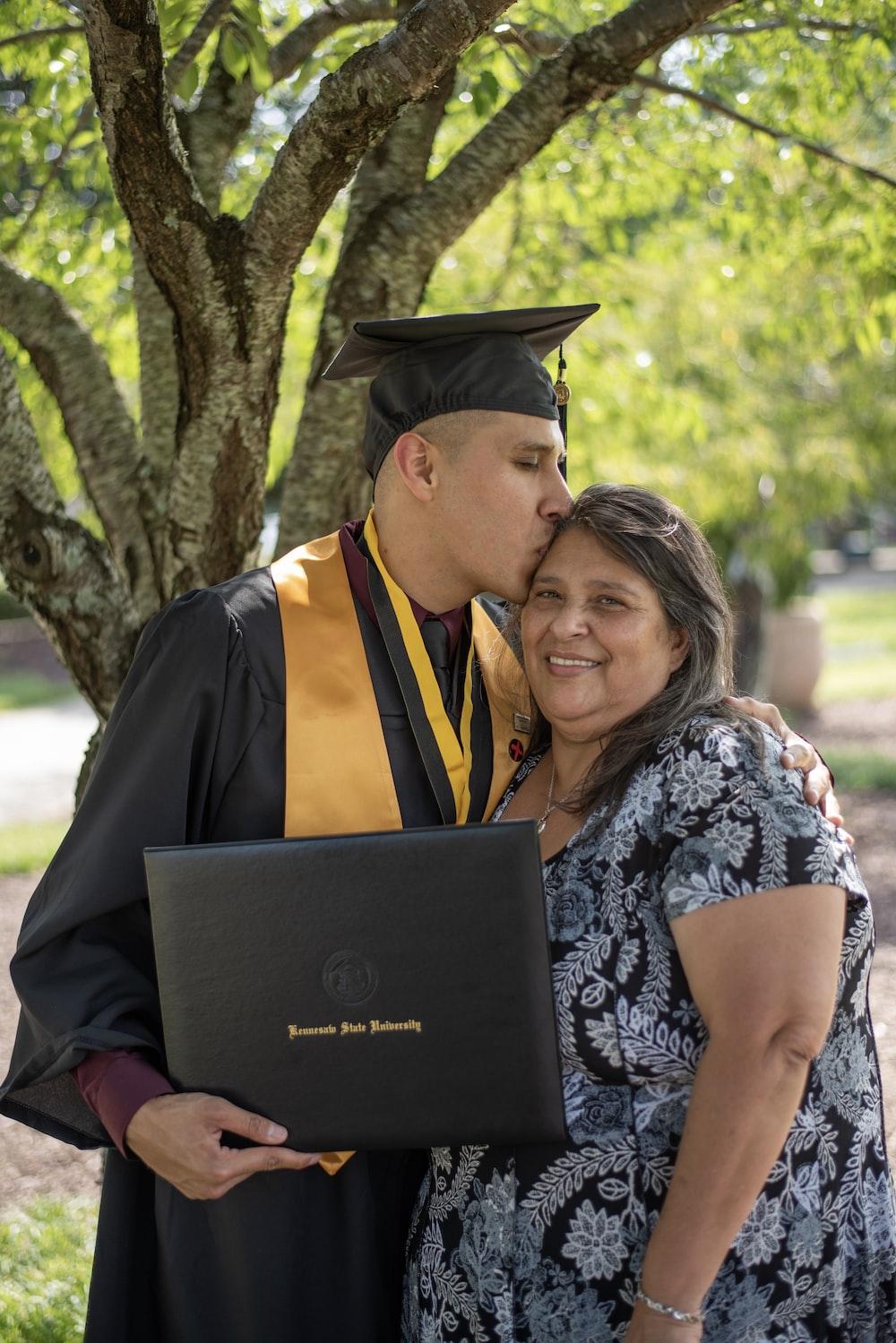 man wearing black graduation gown kissing on woman head