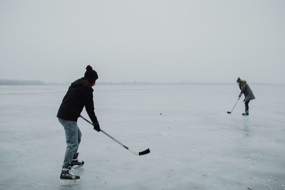 2 people playing hokey on ice