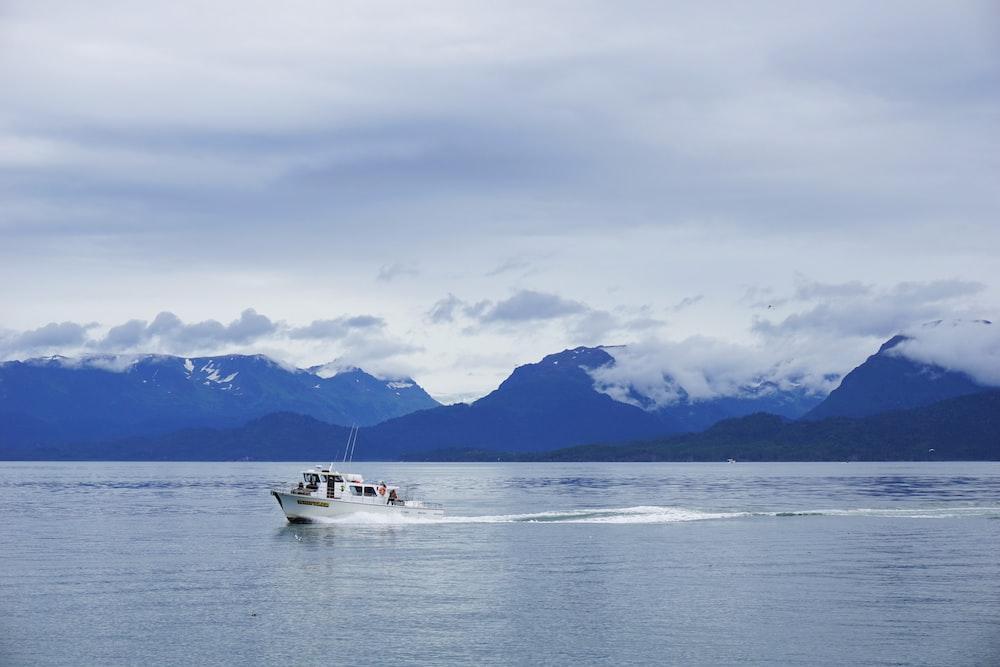 white boat on sea near mountain view