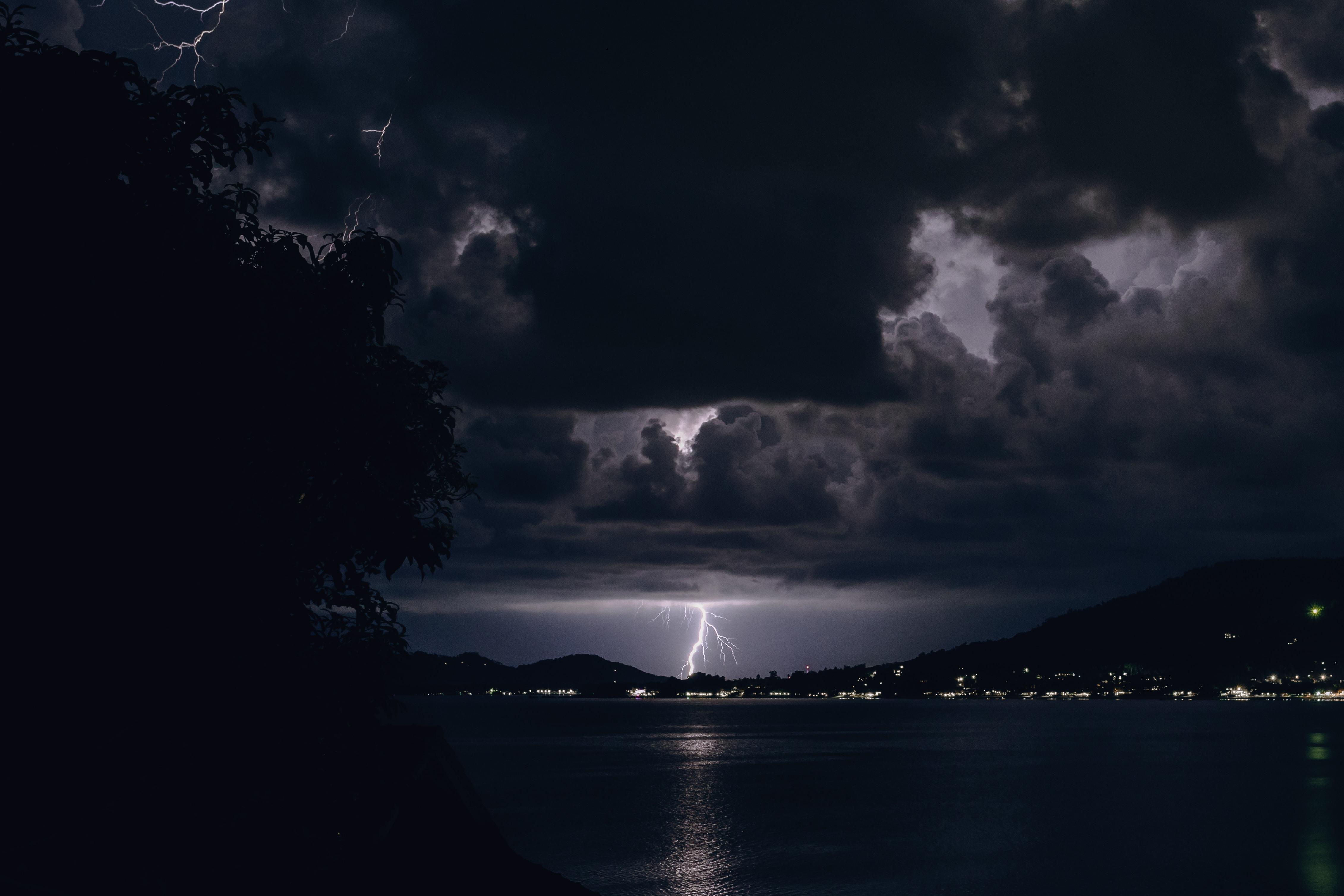 body of water near town under dark clouds