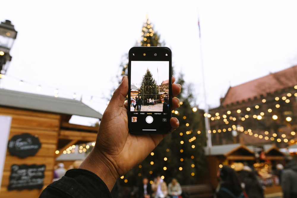 person taking photo of Christmas tree