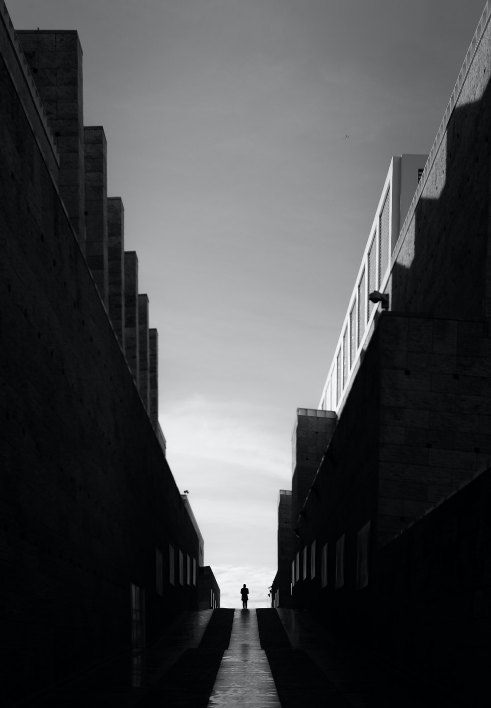 greyscale photo of pathway between buildings
