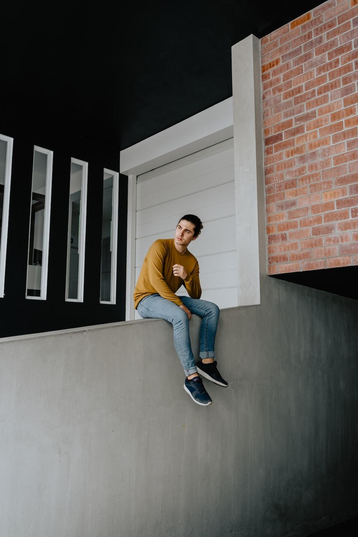 man sitting on gray wall